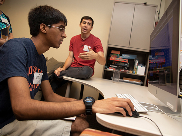 Student works at computer with person advising